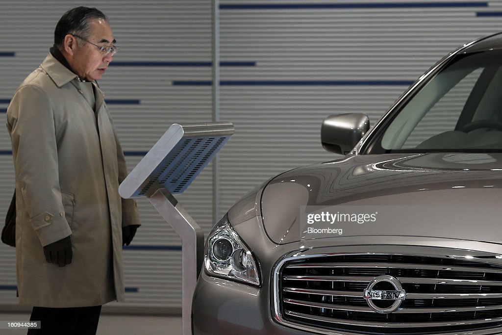 A customer looks at an information panel next to a Nissan Motor Co. Cima sedan displayed at the company's showroom in Yokohama, Kanagawa Prefecture, Japan, on Friday, Feb. 8, 2013. Nissan, Japan's second-biggest carmaker, reported third-quarter profit that fell short of analysts' estimates, after sales tumbled in China and new models trailed competitors in the U.S. Photographer: Kiyoshi Ota/Bloomberg via Getty Images