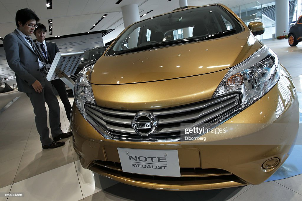 A customer looks at an information panel next to a Nissan Motor Co. Note Medalist vehicle displayed at the company's showroom in Yokohama, Kanagawa Prefecture, Japan, on Friday, Feb. 8, 2013. Nissan, Japan's second-biggest carmaker, reported third-quarter profit that fell short of analysts' estimates, after sales tumbled in China and new models trailed competitors in the U.S. Photographer: Kiyoshi Ota/Bloomberg via Getty Images