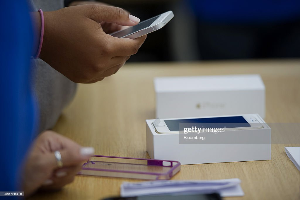 A customer looks at an iPhone 6 during the sales launch at the Apple Inc. store in Palo Alto, California, U.S., on Friday, Sept. 19, 2014. Apple Inc.'s stores attracted long lines of shoppers for the debut of the latest iPhones, indicating healthy demand for the bigger-screen smartphones. The larger iPhone 6 Plus is already selling out at some stores across the U.S. Photographer: David Paul Morris/Bloomberg via Getty Images