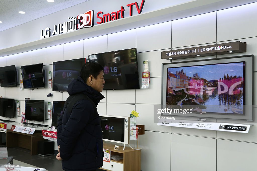 A customer looks at an LG Electronics Inc. organic light-emitting diode (OLED) television, which uses an LG Display Co. panel, at the company's Bestshop store in Seoul, South Korea, on Wednesday, Jan. 22, 2014. LG Electronics, the worlds second-largest seller of televisions, is scheduled to announce fourth-quarter earnings on Jan. 27. Photographer: SeongJoon Cho/Bloomberg via Getty Images