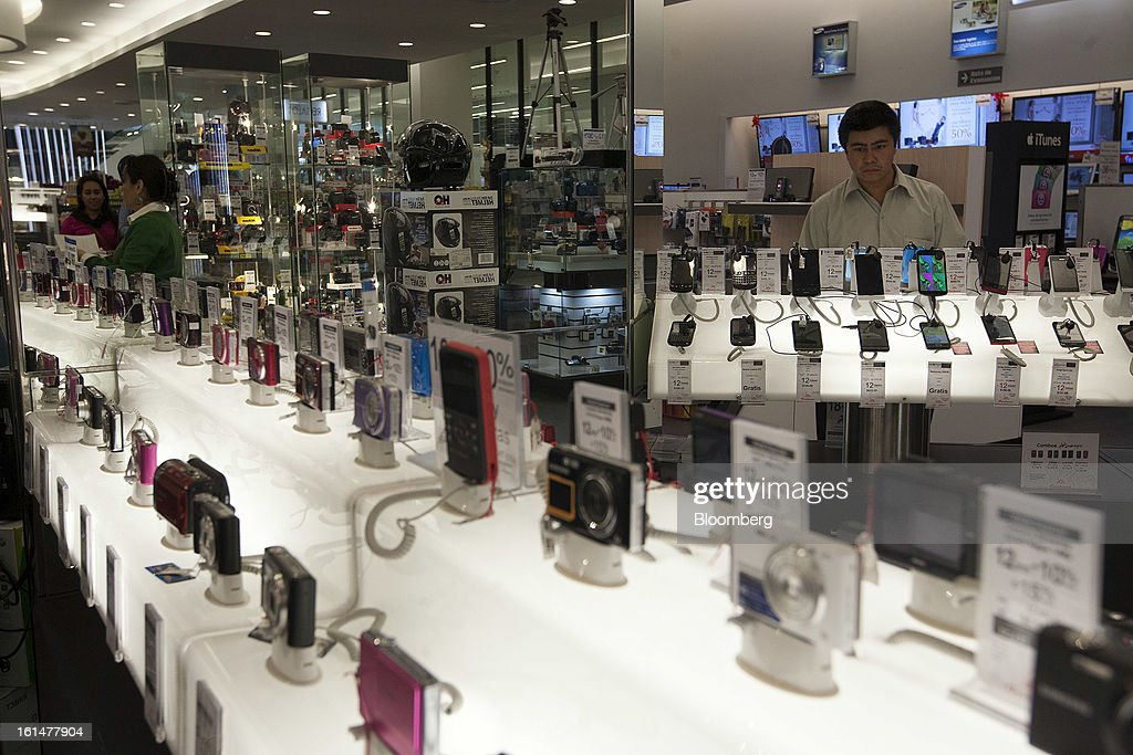 A customer looks at Apple Inc. iPhones at a Grupo Sanborns SAB store in the Plaza Carso development in Mexico City, Mexico, on Friday, Feb. 8, 2013. Grupo Sanborns SAB, the retailer controlled by Mexican billionaire Carlos Slim, raised 10.5 billion pesos ($825 million) in an initial public offering (IPO) last week and the total could climb to 12.1 billion pesos including an overallotment option for underwriters. Photographer: Susana Gonzalez/Bloomberg via Getty Images