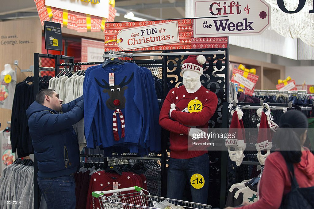 A customer looks at Christmas themed jumpers displayed for sale in the clothing department of an Asda supermarket in Wembley, London, U.K., on Friday, Nov. 29, 2013. Britons queued outside Asda supermarkets this morning and charged into stores when doors opened at 8 a.m. as the U.K. grocery chain took on the Black Friday mantle from U.S. owner Wal-Mart Stores Inc. Photographer: Simon Dawson/Bloomberg via Getty Images