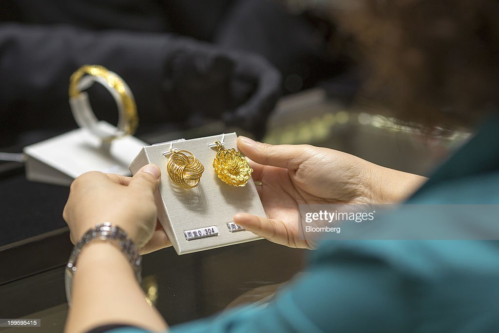 A customer looks at gold pendants in a Chow Tai Fook Jewellery Group Ltd. store in the Central district of Hong Kong, China, on Wednesday, Jan. 16, 2013. Chow Tai Fook Jewellery, the world's biggest jeweler by market value, posted an 8 percent drop in third-quarter same-store sales as Chinese shoppers curbed spending amid a slower economy. Photographer: Jerome Favre/Bloomberg via Getty Images