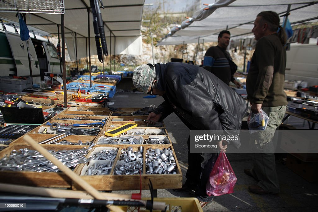 A customer looks at goods for sale on a metal hardware stall at the 'Bazaar of Schisto' open market in Piraeus, Greece, on Sunday, Nov. 18, 2012. European finance ministers aim to stitch together Greece's next aid payment as a sputtering euro-area economy and a spat with the International Monetary Fund cloud efforts to resolve the debt crisis. Photographer: Kostas Tsironis/Bloomberg via Getty Images