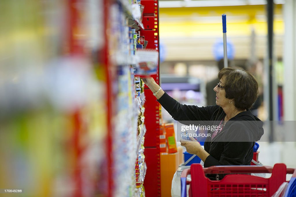A customer looks at goods in a rack of a Carrefour supermarket, on June 14, 2013 in Sainte-Geneviève-des-Bois, outside Paris. Installed in Sainte-Geneviève-des-Bois since fifty years, on June 15, 1963, this supermarket is the first of French giant retailer Carrefour group, but also the first in France.