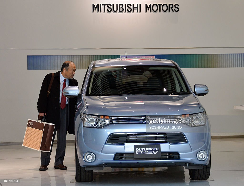 A customer looks at Mitsubishi Motors' new plug-in hybrid SUV 'Outlander PHEV' at the company's showroom in Tokyo on February 5, 2013. Mitsubishi Motors said its group net profit in the nine months April to December rose 27.3 percent from a year earlier to 17.34 billion yen due to cost-cutting efforts. AFP PHOTO / Yoshikazu TSUNO