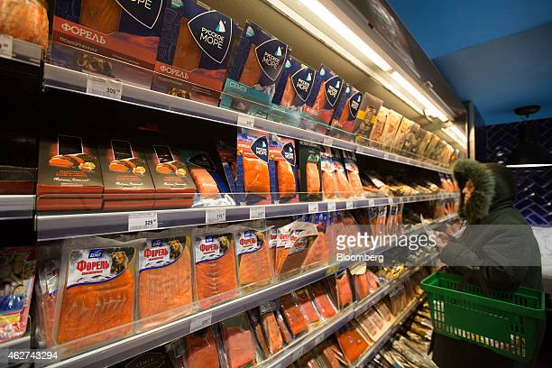 A customer looks at packets of chilled salmon as they sit on display inside a Perekrestok supermarket operated by X5 Retail Group in Moscow Russia on...