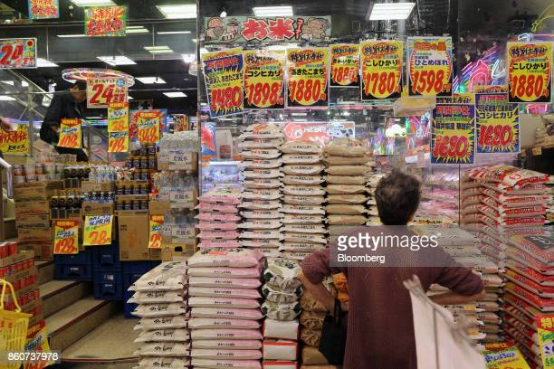 A customer looks at prices for rice at a Super Tamade KK supermarket in the Tenjinbashi district of Osaka Japan on Monday Oct 9 2017 Amid the gloom...