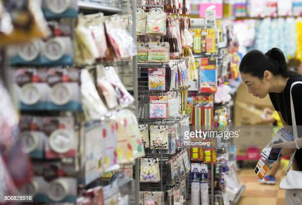 A customer looks at products on display at a Daiso store operated by Daiso Sangyo Corp in the Harajuku area of Tokyo Japan on Friday June 30 2017...