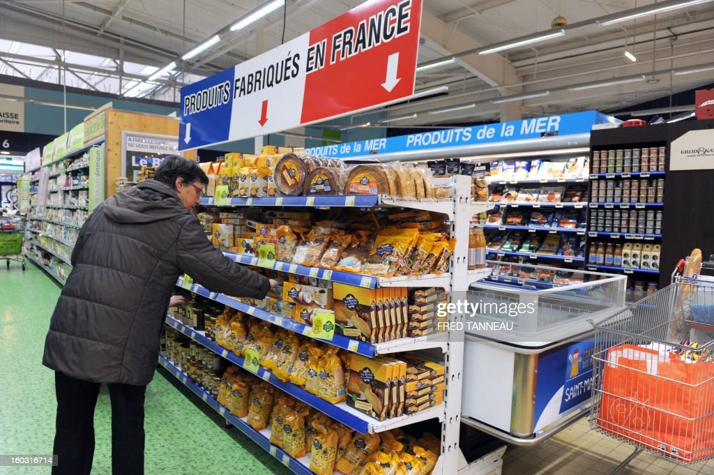 A customer looks at shelves with 'Made in France' products on January 29, 2013 in a Leclerc hypermarket in Lanester, western of France. The distribution group Leclerc test in several of his stores shelves 'made in France' requested by French Industrial Renewal Minister Arnaud Montebourg, and gives a year to 'optimize' the concept, said his boss Michel-Edouard Leclerc.