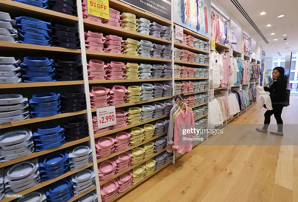 A customer looks at shirts displayed at Fast Retailing Co.'s Uniqlo store in the Ginza district of Tokyo, Japan, on Wednesday, April 10, 2013. Fast Retailing, Asia's largest apparel retailer, is scheduled to announce earnings tomorrow. Photographer: Yuriko Nakao/Bloomberg via Getty Images