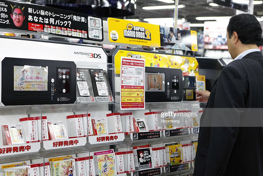 A customer looks at software titles for Nintendo Co.'s 3DS handheld game console at an electronics store in Tokyo, Japan, on Wednesday, Oct. 24, 2012. Nintendo, the world's largest maker of video-game machines, cut its full-year profit forecast amid weaker demand for its 3DS handheld player and a strong yen. Photographer: Kiyoshi Ota/Bloomberg via Getty Images