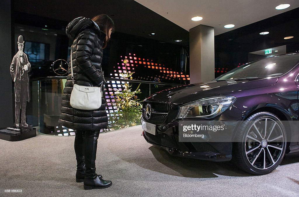 A customer looks at the front of a Mercedes-Benz CLA 180 Coupe automobile, produced by Daimler AG, inside the Mercedes-Benz Gallery showroom in Berlin, Germany, on Thursday, Dec. 19, 2013. European new-car sales rose a third consecutive month in November, the longest period of gains in four years. Photographer: Krisztian Bocsi/Bloomberg via Getty Images