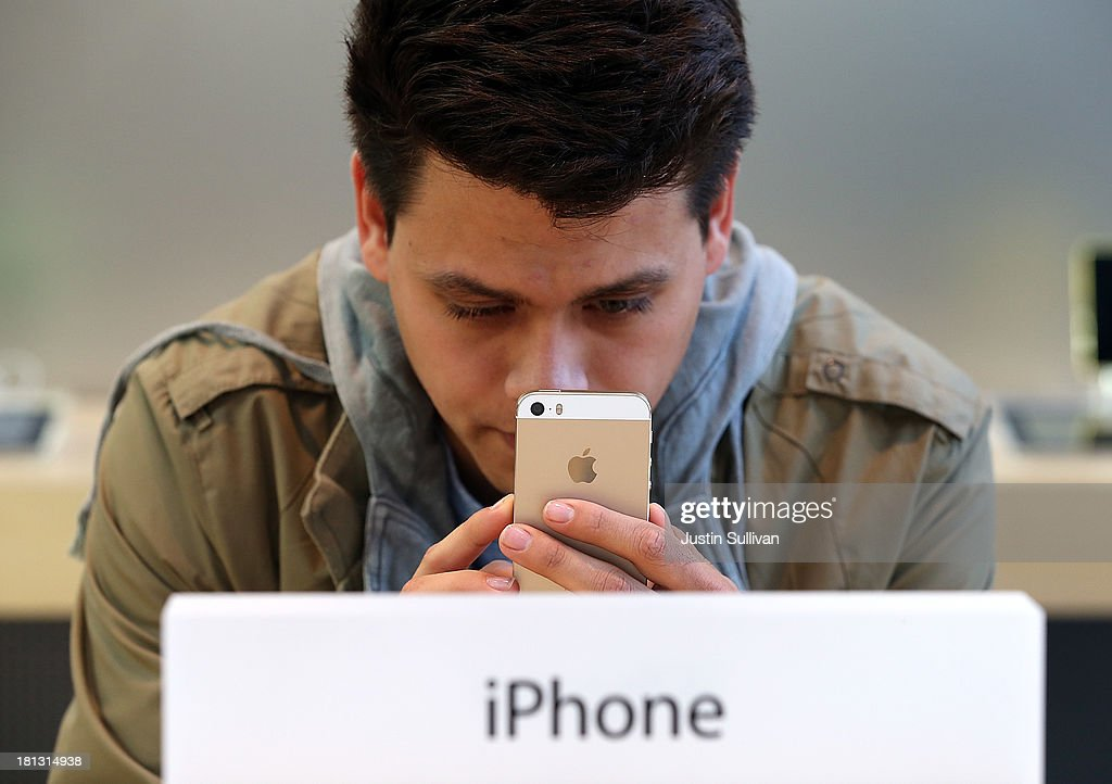 A customer looks at the new Apple iPhone 5S at an Apple Store on September 20, 2013 in Palo Alto, California. Apple launched two new models of iPhone: the iPhone 5S, which is preceded by the iPhone 5, and a cheaper, paired down version, the iPhone 5C. The phones come with a new operating system.