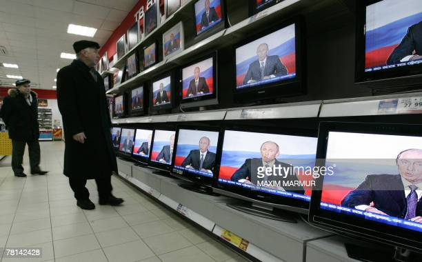 A customer looks at TV sets on display in Moscow shop showing Russian President Vladimir Putin's address to the nation 29 November 2007 Putin warned...