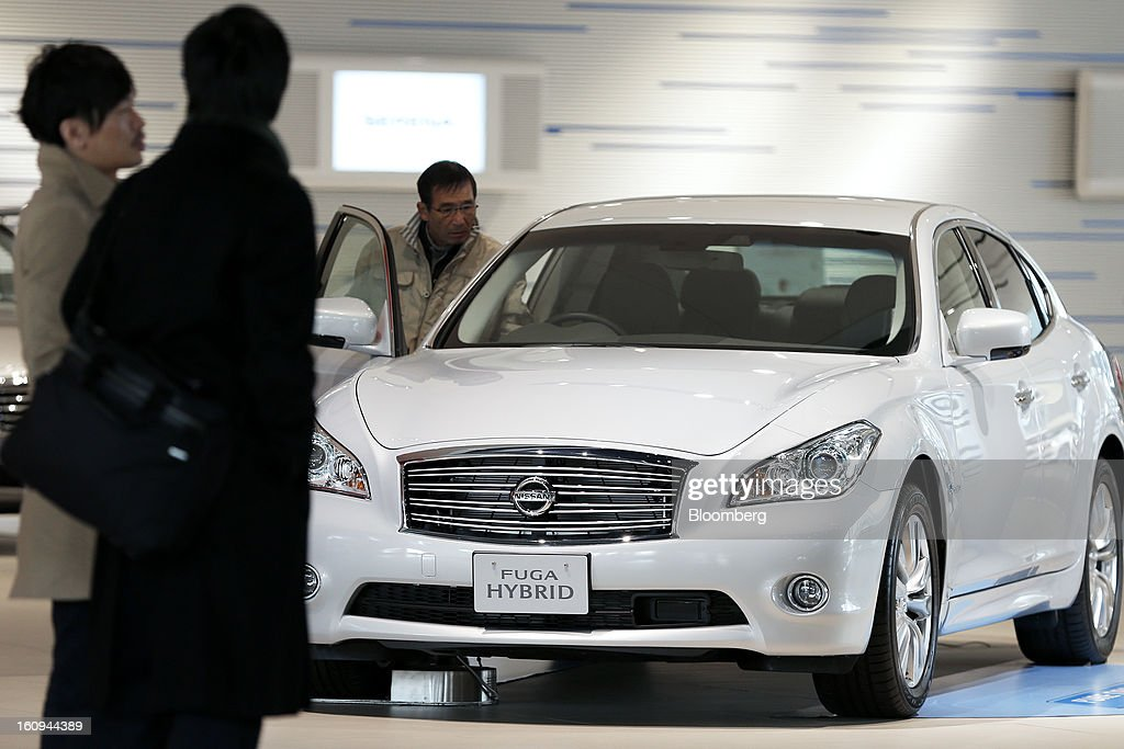 A customer looks inside a Nissan Motor Co. Fuga hybrid vehicle displayed at the company's showroom in Yokohama, Kanagawa Prefecture, Japan, on Friday, Feb. 8, 2013. Nissan, Japan's second-biggest carmaker, reported third-quarter profit that fell short of analysts' estimates, after sales tumbled in China and new models trailed competitors in the U.S. Photographer: Kiyoshi Ota/Bloomberg via Getty Images