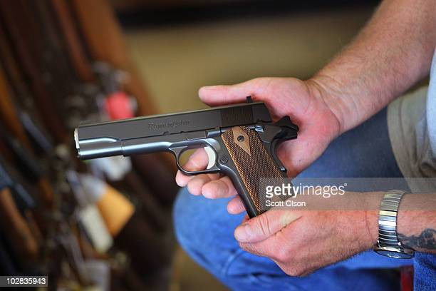 A customer looks over a 45 Caliber pistol at Rinks Gun and Sport in suburban Chicago on July 12 2010 in Lockport Illinois Chicago began enforcing its...