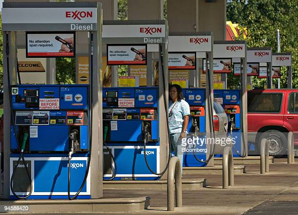 A customer looks over a gasoline pump at an Exxon station in Columbus Ohio US on Thursday Sept 13 2007 Exxon Mobil Corp surpassed PetroChina Co as...