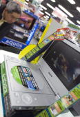A customer looks through Sanyo Electric Co's portable DVD players at an electronics store in Tokyo Japan on Thursday November 23 2006 Shares in Sanyo...