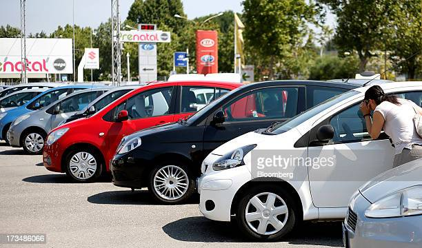 A customer looks through the driver's window of a Toyota automobile displayed for sale outside second hand car dealership in Rome Italy on Saturday...