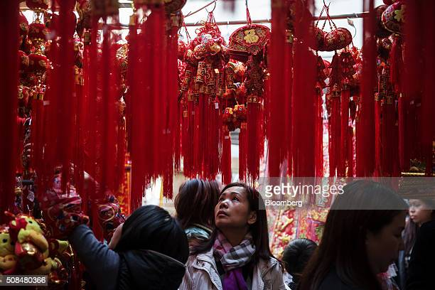 A customer looks up at decorations on sale for Lunar New Year at a market stall in the Sham Shui Po district of Hong Kong China on Thursday Feb 4...
