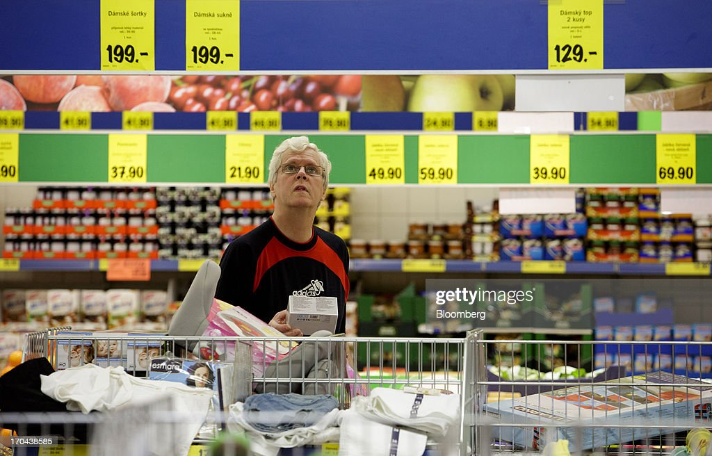 A customer looks up at price signs above a display of goods for sale inside a Lidl discount supermarket store, operated by Schwarz Group, in Prague, Czech Republic, on Thursday, June 13, 2013. Ahold and Tesco are tied as the Czech Republic's third-largest grocer by revenue behind Lidl discount store owner Schwarz Group and Rewe AV, which owns the Billa supermarkets, according to Krakow, Poland-based market researcher PMR. Photographer: Martin Divisek/Bloomberg via Getty Images