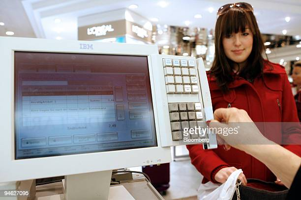 Customer Maike Wende makes a purchase with a credit card in the Wertheim department store owned by Karstadt in Berlin Germany Friday December 29 2006