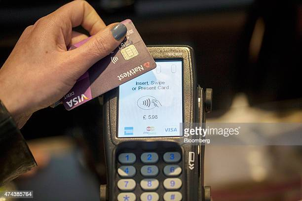 A customer makes a contactless payment using a Natwest Visa Inc debit card via a Verifone Systems Inc payment device which also supports payments by...