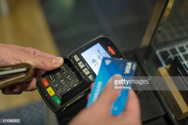A customer makes a contactless payment with a bank card on an Ingenico Iberia SL payment device in London UK on Friday May 22 2015 Credit and debit...
