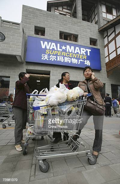 A customer makes a phone call after shopped in Chongqing's second WalMart store which opened today November 16 2006 in Chongqing Municipality China...