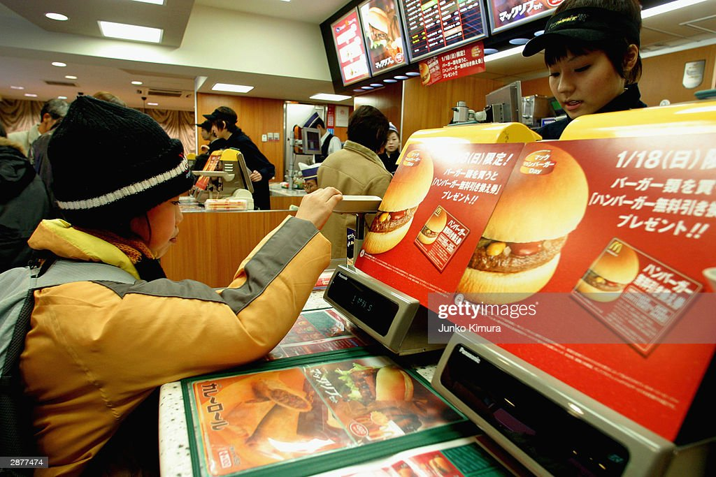 Customer makes a purchase in a McDonalds January 18 2004 in Tokyo Japan McDonald's in Japan are planning to give out some 10 million coupons for free...