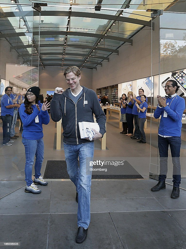 Customer Noah Wasmer smiles while walking out with a new Apple Inc. iPad Air on the first day of sales at a store in Palo Alto, California, U.S., on Friday, Nov. 1, 2013. Apple Inc.'s forecast for the slowest holiday sales growth in a half decade reflects how iPhones and iPads aren't providing the growth surges they once did as competition accelerates in the saturated mobile market. Photographer: Tony Avelar/Bloomberg via Getty Images