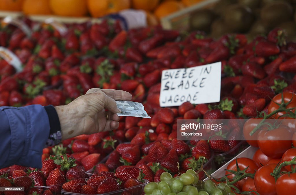 A customer offers a euro note for payment at an open market in Ljubljana, Slovenia, on Wednesday, May 8, 2013. Slovenia's recession will stretch into next year on weak domestic demand as the euro-area country teeters on the brink of needing an international bailout, the European Commission said. Photographer: Chris Ratcliffe/Bloomberg via Getty Images