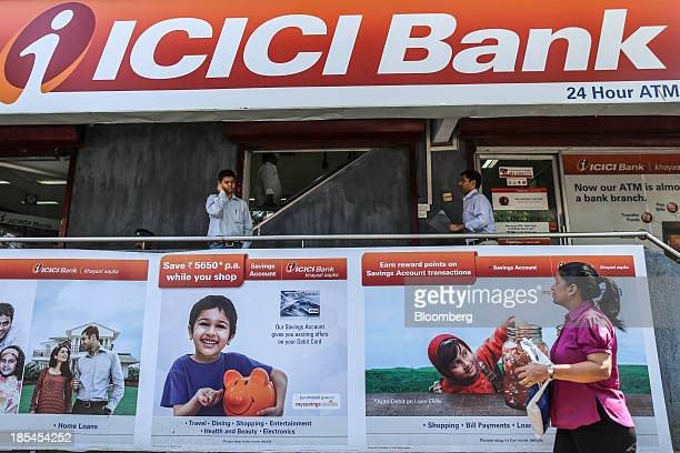 A customer on a mobile device exits a branch of ICICI Bank Ltd in Mumbai India on Saturday Oct 19 2013 ICICI Bank is scheduled to release quarterly...