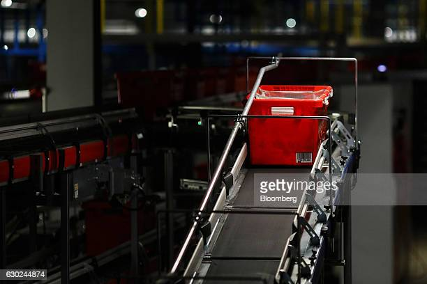 A customer order crate travels along a conveyor belt at the Ocado Group Plc distribution centre in Dordon UK on Friday Dec 16 2016 Ocado provides...