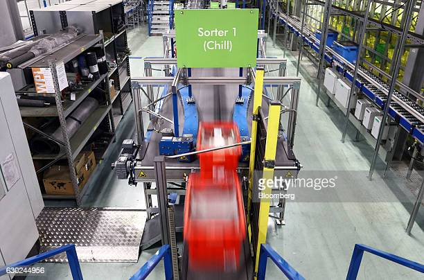 Customer order crates travel along a conveyor belt in the chilled section at the Ocado Group Plc distribution centre in Dordon UK on Friday Dec 16...