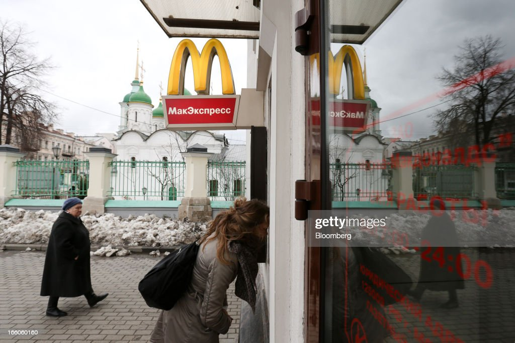 A customer orders her meal from a service window outside a McDonald's food restaurant in Moscow, Russia, on Sunday, April 7, 2013. McDonald's Corp., which virtually created the market for burgers and fries in the country and convinced Russians it's OK to eat with their hands, must fend off a growing challenge from rivals Burger King Worldwide Inc., Subway Restaurants, Yum! Brands Inc. and Wendy's Co. Photographer: Andrey Rudakov/Bloomberg via Getty Images