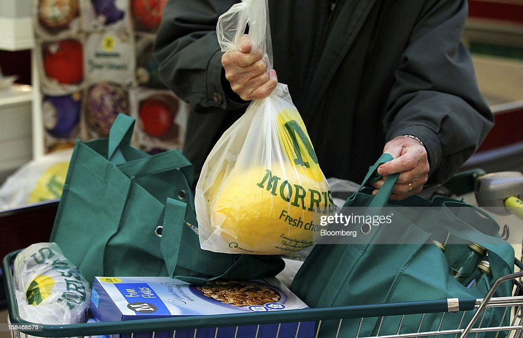 A customer packs his shopping cart after paying for his goods at a Morrisons supermarket, operated by William Morrsons Supermarkets Plc, in Chadderton, U.K., on Monday, Dec. 17, 2012. The British Christmas is the biggest epicurean occasion of the year, with households spending a total of 4 billion pounds on food in the final week before Dec. 25. Photographer: Paul Thomas/Bloomberg via Getty Images