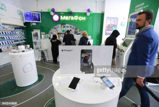 A customer passes a display of Apple Inc iPhone 7 smartphones inside a MegaFon PJSC mobile phone store in Moscow Russia on Tuesday Aug 29 2017...