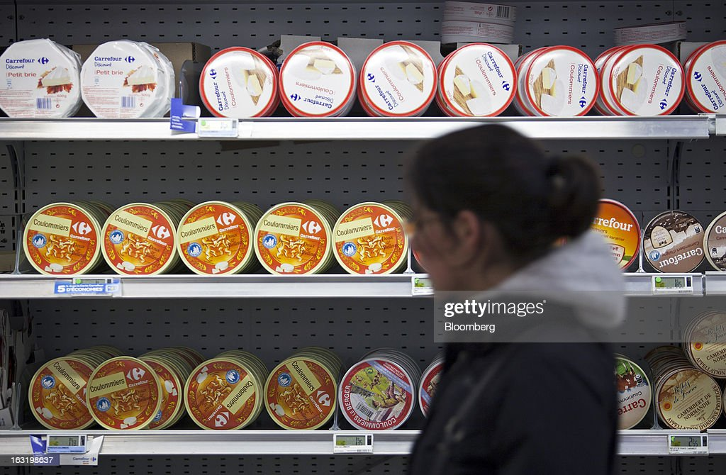 A customer passes a display of Carrefour-branded cheeses in the chilled food aisle of a Carrefour SA supermarket in Portet sur Garonne, near Toulouse, France, on Tuesday, March 5, 2013. Carrefour's stock has risen 47 percent since Georges Plassat's arrival as chief executive officer, partially offsetting a 71 percent decline in the preceding five years. Photographer: Balint Porneczi/Bloomberg via Getty Images