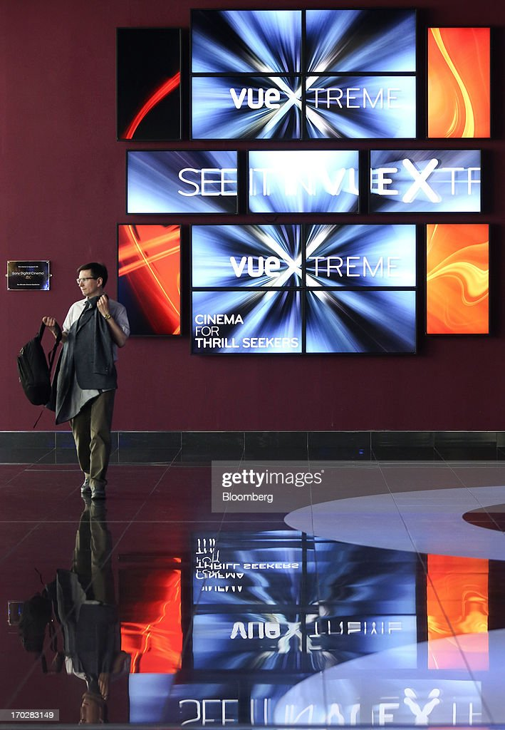 A customer passes a multi-screen display in the lobby of a Vue Cinema, operated by Vue Entertainment Ltd., at the Westfield Stratford City retail complex in London, U.K., on Tuesday, June 4, 2013. Vue Entertainment, the U.K. cinema chain bought by private equity firm Doughty Hanson & Co., are continuing to expand in Europe, recently acquiring Poland's second-largest cinema chain Multikino. Photographer: Chris Ratcliffe/Bloomberg via Getty Images