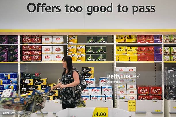 A customer passes a sign which reads 'Offers too good to pass' as she pushes a shopping cart past a display of boxed lager beer and cider inside a...