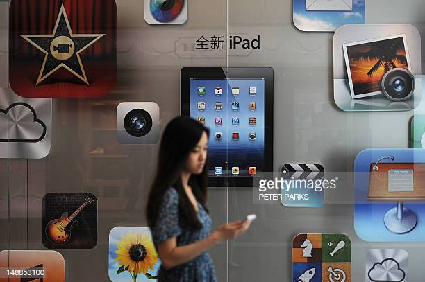 A customer passes an Apple store where the latest version of the Apple iPad went on sale in Apple stores in Shanghai on July 20 2012 Apple began...