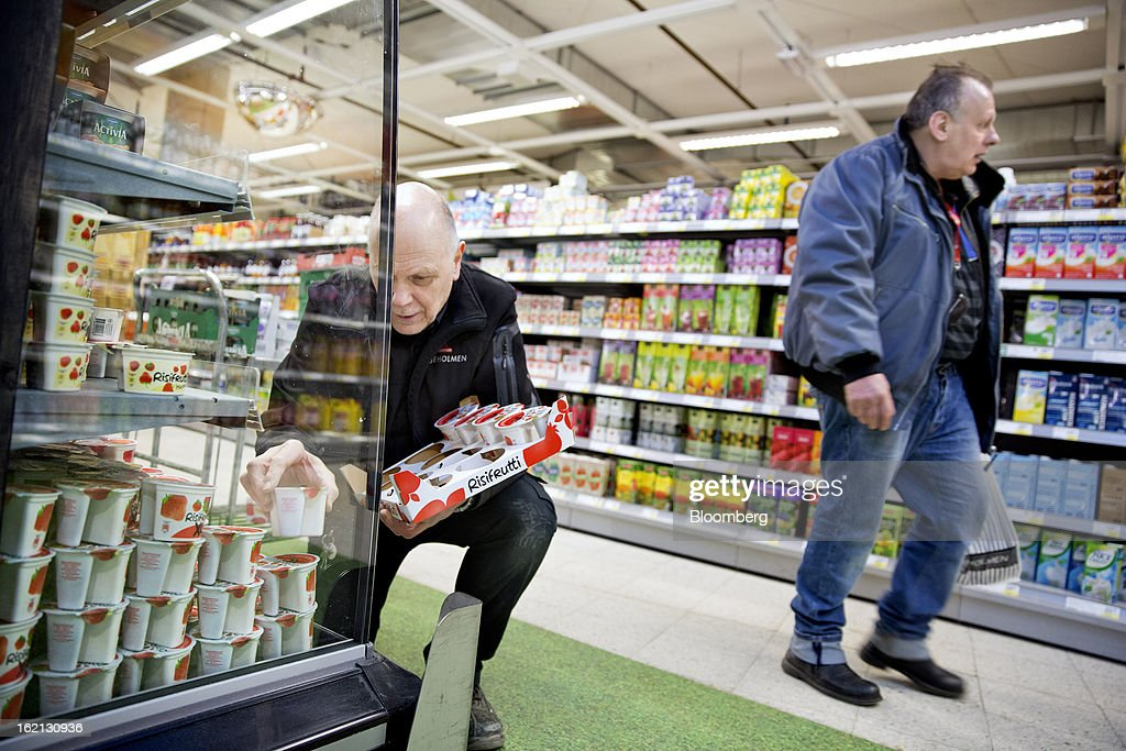 A customer passes an employee as he restocks a chilled display cabinet with dairy products inside an ICA supermarket store in Stockholm, Sweden, on Tuesday, Feb. 19, 2013. Hakon Invest AB, the minority owner of Sweden's largest food retailer ICA, agreed to take full control by acquiring partner Royal Ahold NV's 60 percent stake for 20 billion kronor ($3.1 billion). Photographer: Casper Hedberg/Bloomberg via Getty Images