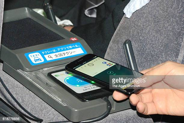 A customer passes his iPhone 7 over a card reader to pay taxi as Apple Pay launches in Japan on October 25 2016 in Tokyo Japan