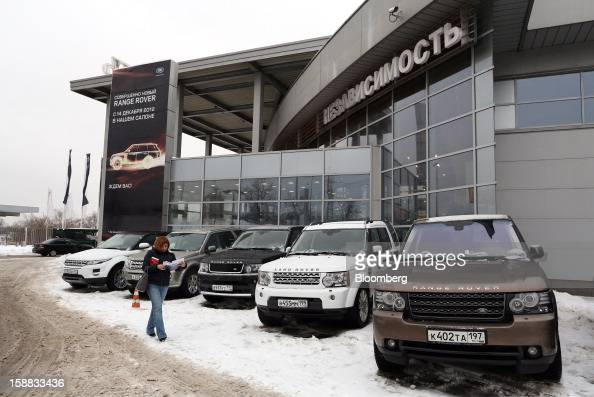 A customer passes Range Rover automobiles used for test drives parked on the forecourt of an independent auto showroom in Moscow Russia on Friday Dec...