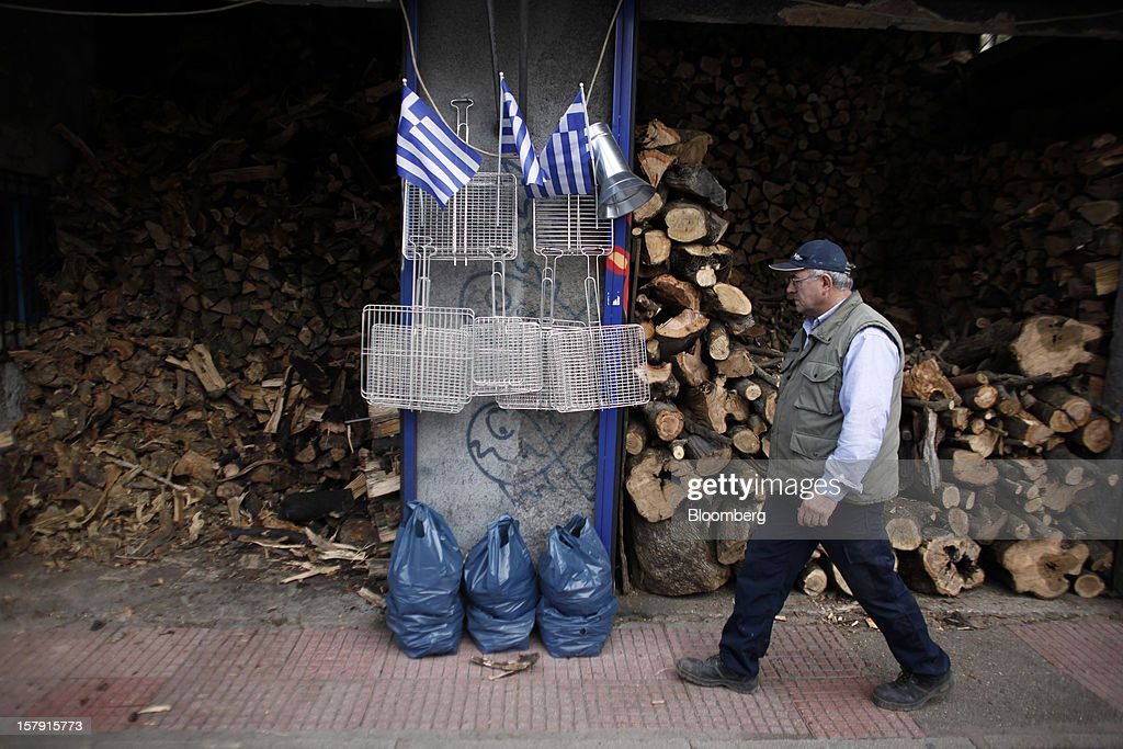 A customer passes stores of firewood at a wood supply store in Athens, Greece, on Friday, Dec. 7, 2012. Greece, the epicenter of Europe's debt crisis since revealing a bloated spending gap in late 2009, has faced regular demands to get a firmer grip on the budget or risk being forced out of the euro. Photographer: Kostas Tsironis/Bloomberg via Getty Images