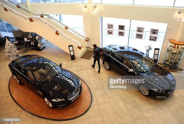 A customer passes two Jaguar XJ series automobiles on display in an independent auto showroom in Moscow Russia on Friday Dec 28 2012 Tata Motors...