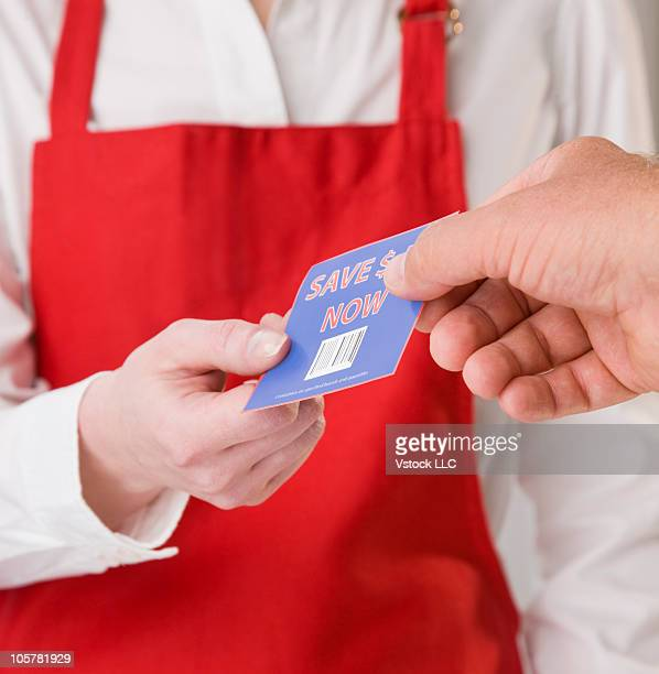 Customer passing shopping coupon to store clerk