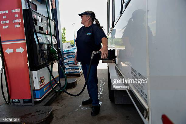 Customer Pat Olds fuels her vehicle at a Road Ranger gas station in Princeton Illinois US on Tuesday June 17 2014 Gasoline in the US climbed this...